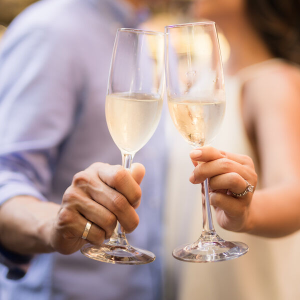 Couple wearing wedding rings holding champagne glasses. Photo by Joshua Chun on Unsplash.com