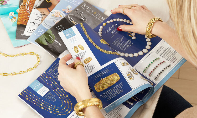 Woman wearing gold jewelry looking at Ross-Simons catalogs.
