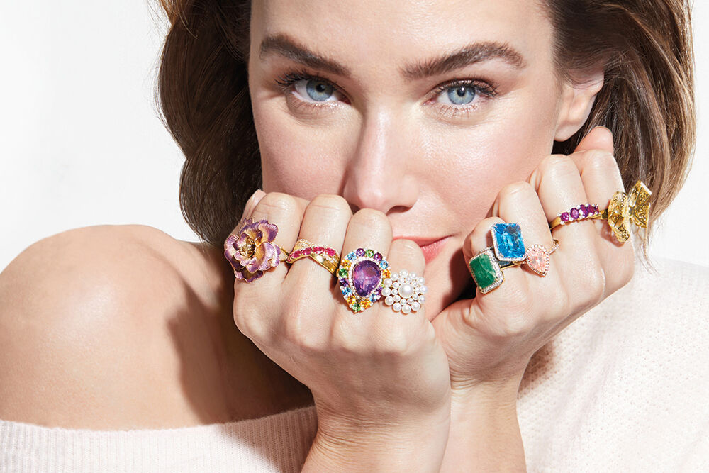 Model wearing different gemstone rings on every finger.