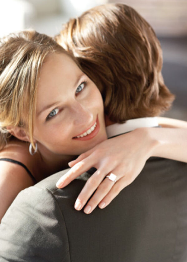 Happy Couple with her wearing diamond ring and earrings.